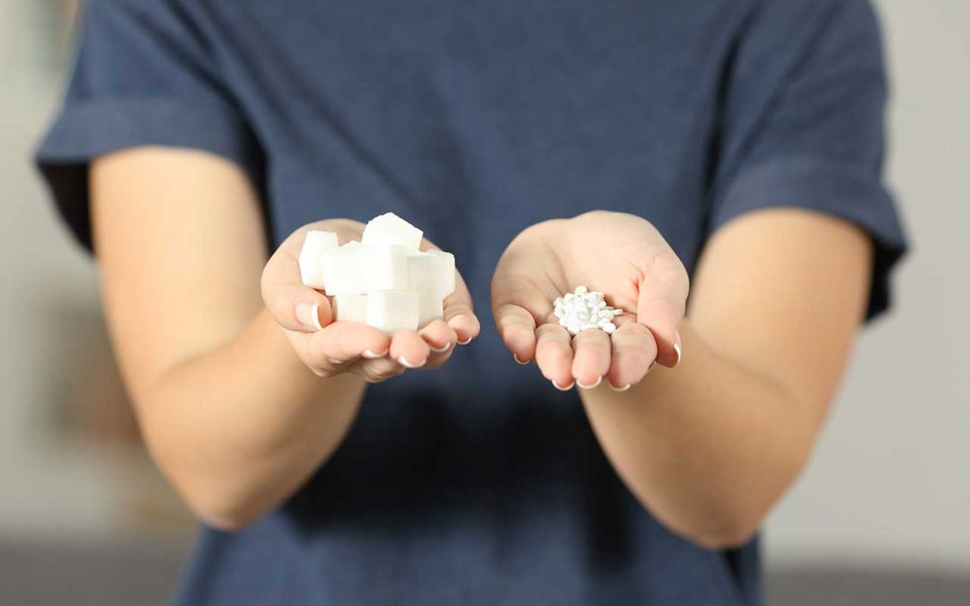 woman holding pills in one hand and sugar cubes in the other