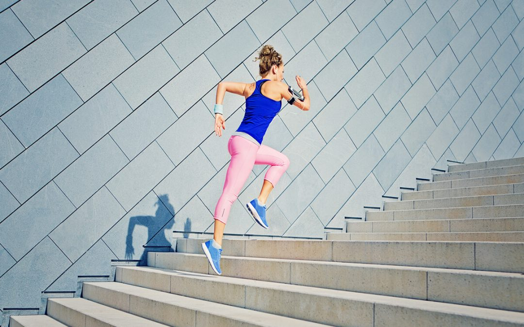 woman in working attire jogging up a flight of steps