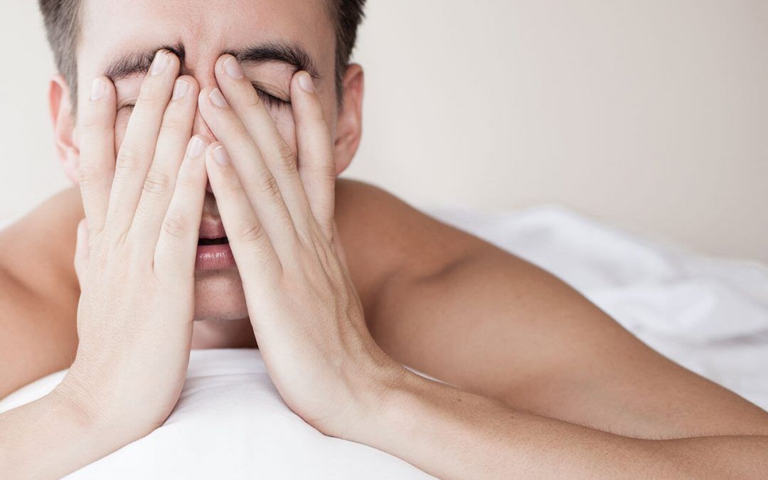 stressed man lying in bed with hands in front of his face