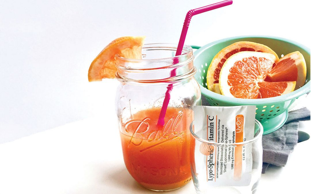 mason jar filled with summer skin drink, bowl of grapefruit, and empty shot glass with packet of lypo spheric vitamin c
