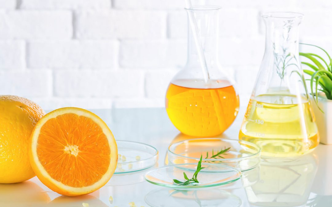 beakers filled with orange liquid on counter with sliced oranges