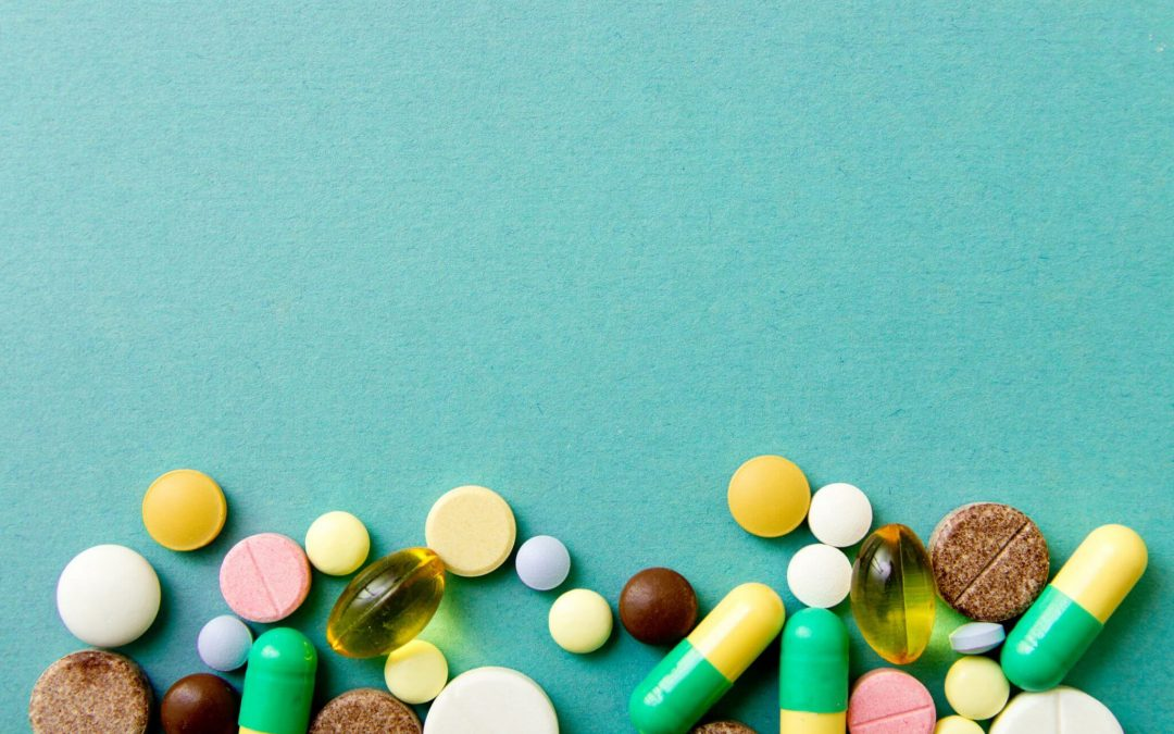 Many colorful pills on red background with copy space