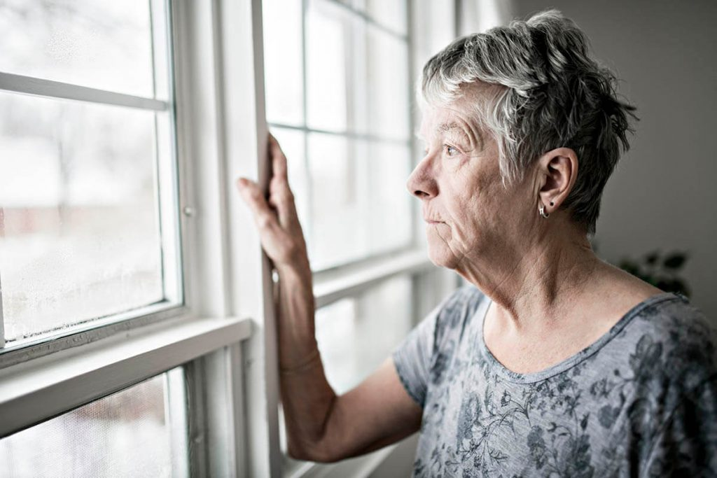 older woman in social isolation looks out the window